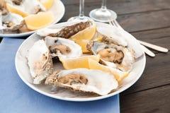 Huîtres fraîches avec le citron juteux de coupe servi photo stock