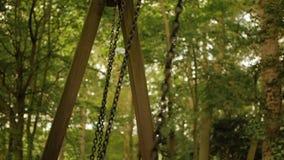 Huśtawka łańcuchy huśtają się wolno od strony strona Zamazany las w tle zdjęcie wideo