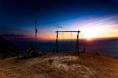 Huśtawkowy obwieszenie przy wierzchołkiem góra przy zmierzchu czasem Zdjęcia Royalty Free
