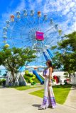 A smiling girl stand in front of the colorful ferris wheel in Santorini Park royalty free stock image