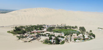 Huacachina Oasis in Ica city in Peru. White sand dunes around green palm trees oasis. Small village with a lake in the middle of the desert small oasis royalty free stock images