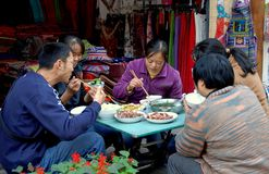 Huang Long Xi, China: Family Dining. Family members sitting at a small table in front of their fabric and clothing shop enjoy lunch in the historic Sichuan Royalty Free Stock Photo
