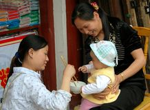 Huang Long Xi, China: Feeding Baby. Grandmother holding baby as her daughter feeds rice to the little girl using chopsticks (kuai zi) in front of their shop in Stock Photography