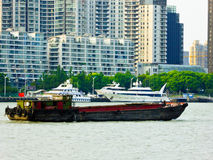 Huangpu river sightseeing boats in Shanghai. Huangpu river yacht and cargo ship with tall modern apartments buildings background in Shanghai China Stock Photo