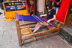 Huangshan Tunxi City, China - circa September 2015: Girl weaves textile using traditional loom  device Royalty Free Stock Photography