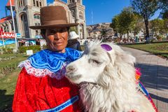 Indigenous woman from Peru. Huaraz, Peru, July 2018: Indigenous woman from Peru, poses with her alpaca, so tourists and visitors can take pictures in exchange stock photography