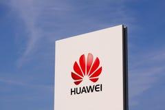 Huawei logotyp na białym panelu znaku kwaterami głównymi z jasnym niebieskim niebem Obraz Royalty Free
