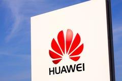 Huawei logotyp na białym panelu znaku kwaterami głównymi z jasnym niebieskim niebem Fotografia Royalty Free