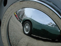 Hub cap reflection. Old English car reflected in hubcap of another Stock Images