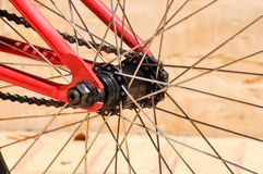 Hub and Spokes. Closeup detail of metal hub and spokes of bicycle wheel including chain detail and painted red metal frame Stock Photography