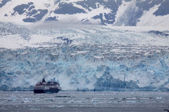 Hubbard Glacier - a cruise ship approaches. A full size cruise ship looks like a toy miniature as it navigates the many icebergs in Disenchantment Bay that have Stock Photography