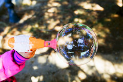 Hubble-bubble. Children with a toy gun blowing bubbles Stock Images