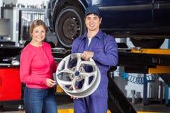 Ευτυχείς μηχανικός και πελάτης με Hubcap Στοκ εικόνες με δικαίωμα ελεύθερης χρήσης