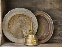 Hubcaps and tall oil can on old garage shelf. Vintage hubcaps and brass oiler with tall spout on weathered wood shelf royalty free stock photography