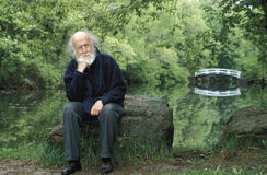 Hubert Reeves. The famous astrophysician author of numerous book, is sitting on a rock with a thinking mood in front of a pond surrounded by big trees giving a Royalty Free Stock Image