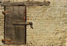 hublot avec le cadenas dans le mur de briques Photo stock