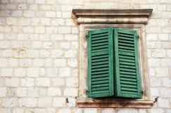 Hublot avec les obturateurs verts dans le vieux mur (Italie) images stock