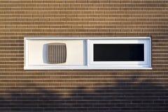 Hublot blanc dans le mur de briques de Brown photographie stock