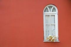 Hublot blanc sur le mur rouge Photographie stock