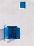 Hublot bleu sur le mur blanc photo stock