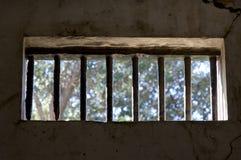 Hublot d'une cellule de prison de l'intérieur, arbres à l'extérieur Photos stock