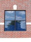 Hublot de quatre Paned sur un mur de briques rouge Image libre de droits
