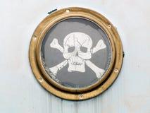 Hublot en laiton sur le bateau avec le drapeau de pirate Images libres de droits