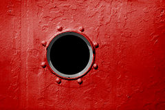 Hublot sur le mur rouge du vieux bateau Photographie stock libre de droits