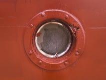 Hublot sur le mur rouge du vieux bateau Photos stock