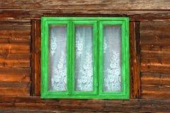 Hublot vert d'une vieille maison rustique avec les murs en bois images stock