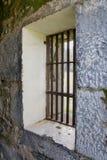 Hublots barrés vieille par prison à l'angle Photos stock