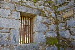 Hublots barrés vieille par prison Image stock