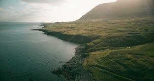 Hubschrauber, der über das Gebirgstal nahe dem Wasser in Island fliegt Vogelperspektive des Ufers des Meeres und der Wiese stock video footage