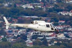 Hubschrauber Eurocopter AS-350BA, der Luftschmierfilmbildung mit einer Nase leitet, brachte Cineflex-Kamera über Melbourne an lizenzfreies stockbild