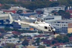 Hubschrauber Eurocopter AS-350BA, der Luftschmierfilmbildung mit einer Nase leitet, brachte Cineflex-Kamera über Melbourne an stockfotos