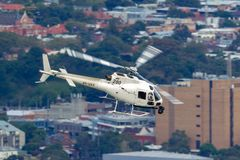 Hubschrauber Eurocopter AS-350BA, der Luftschmierfilmbildung mit einer Nase leitet, brachte Cineflex-Kamera über Melbourne an stockbilder