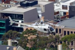 Hubschrauber Eurocopter AS-350BA, der Luftschmierfilmbildung mit einer Nase leitet, brachte Cineflex-Kamera über Melbourne an stockfoto