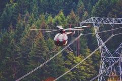 Hubschrauber-Fliegen nahe bei Stromleitungen lizenzfreie stockfotografie
