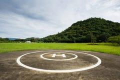Hubschrauber-Landeplatz im Park mit Bergen stockfotografie