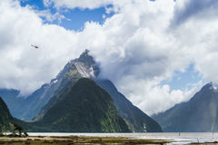 Hubschrauberfliegen hinter dem riesigen Gehrungsfugen-Spitzenberg des Milf stockbilder
