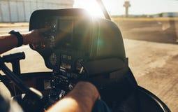 Hubschrauberpilot, der Messgeräte auf dem Instrumentenbrett überprüft Lizenzfreies Stockbild