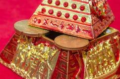 Hucha bajo la forma de pirámide con las monedas en un fondo rojo foto de archivo libre de regalías