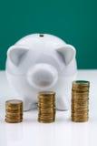 Hucha blanca con la pila de monedas Foto de archivo libre de regalías
