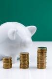 Hucha blanca con la pila de monedas Imagen de archivo libre de regalías