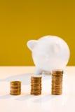 Hucha blanca con la pila de monedas Fotografía de archivo