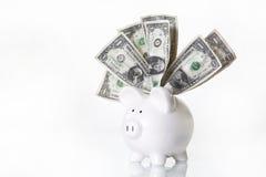 Hucha blanca con los dólares de EE. UU. Foto de archivo libre de regalías