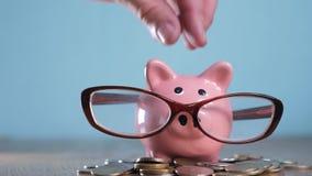 Hucha con concepto del financiero del contable de los vidrios Dinero y hucha crecientes del paso de la pila de la pila del dinero metrajes