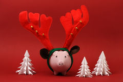 Hucha con el cuerno y los cascabeles del reno que se colocan en fondo rojo con el fondo blanco de la Navidad de tres árboles de l Imagen de archivo libre de regalías