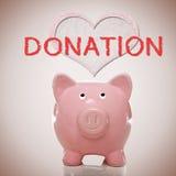 Hucha con el texto del corazón y de la donación Imagenes de archivo