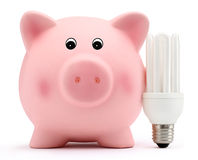 Hucha con la lámpara ahorro de energía en el fondo blanco Imagenes de archivo